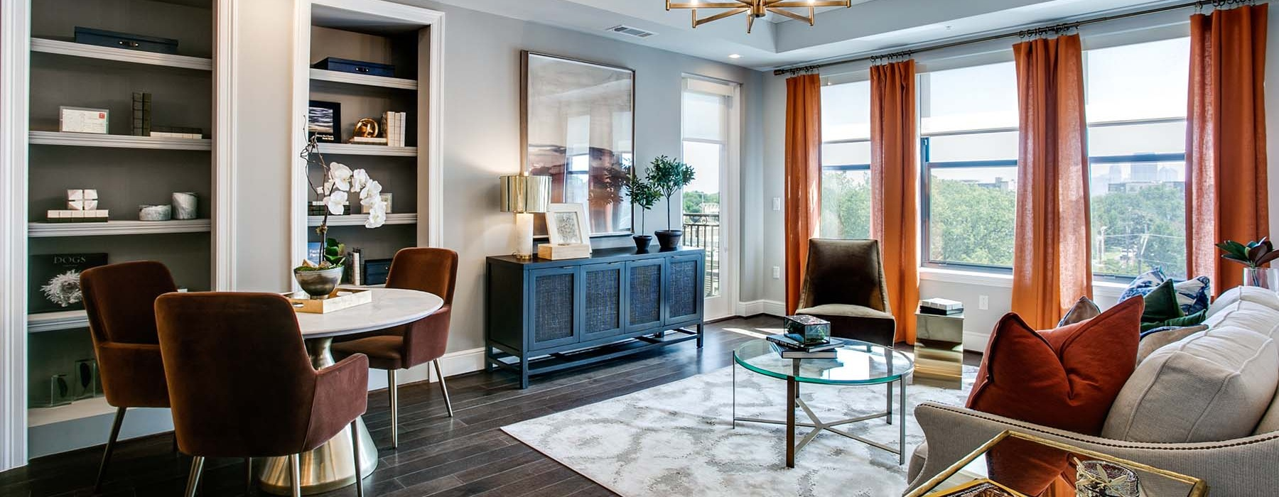 Living features multiple large windows and built-in bookcases